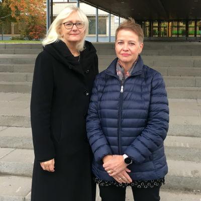Två kvinnor står utomhus framför en trappa och ser in i kameran.