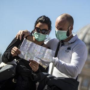 Två personer i munskydd står och tittar på en karta i Italien.