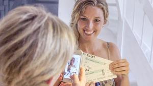 Mette tar en bild på sig själv och biljetterna för att sätta upp på sociala medier.