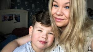 Linn håller om sin son Alex när de både småler in i kameran.