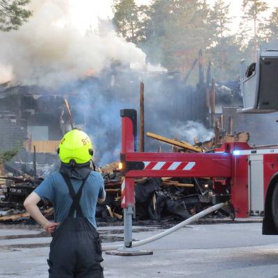 Hiittenharjun hotelli palaa Harjavallassa 14.7.2021, palomies katselee tilannetta paitahihasillaan helteisenä iltana, kuvassa myös paloauto. Savu kohoaa.