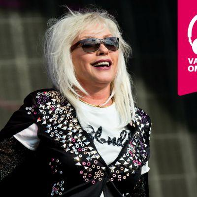 Debbie Harry ler och håller en mikrofon i höger hand.
