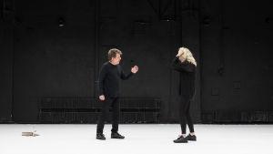 Timo Torikan näyttelemä mies ja Katariina Kaitueen näyttelemä nainen seisovat kasvotusen tyhjällä näyttämöllä ja riitelevät.