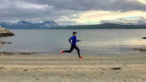 Nainen juoksee Jäämeren rannalla Norjassa.
