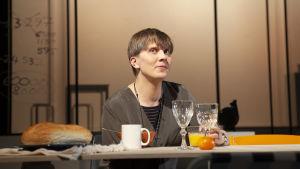 Eero Ritalan näyttelemä nainen istuu hymyillen ruokapöydän ääressä, edessään viinilaseja, kahvikuppeja, hedelmiä ja leipää.