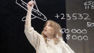 Laura Rämän näyttelemä lapsi piirtää ikkunaan lentokonetta.