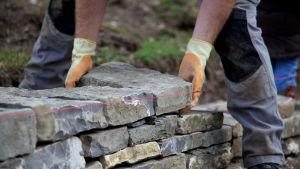 Mies pinoaa kivimuuria.