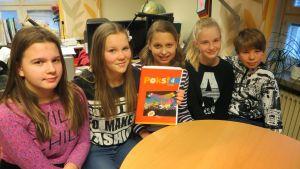 Fem elever som ler och en av dem håller i en bok.