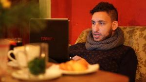 Mies kahvilassa työskentelee tietokoneella