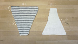 Två trekantiga virkade lappar, en vit och en grå-vit-randig.