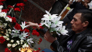 Rysk man placerar blommor efter terrorattacken i S:t Petersburg den 3 april.