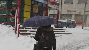 Kvinna går med paraply i slaskvädret
