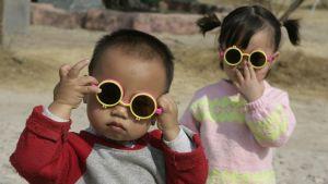 Två sm¨å barn med solglasögon.