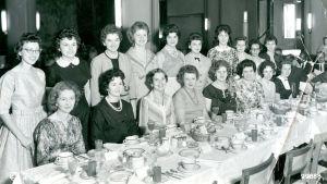 Svartvit bild på kvinnor vid middagsbord.