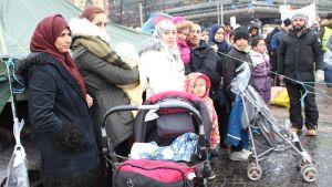 kvinnor med huvuddukar och barnvagnar utanför tältdemonstration i Hfrs
