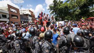 Kravallpolis i förgrunden då regeringsanhängare och -motståndare hotar att drabba samman i Caracas under den informella folomröstningen 16.7.2017