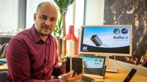 Professor Jaan Praks, Aalto-universitetet, med en Cubesat-satellit i handen.