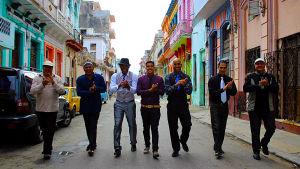 Sju män går i bredd på en gata i Havanna.