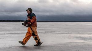 Fiskare Ulf Granqvist går över isen med en isborr i handen