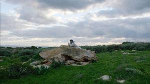 Samuele ligger på en sten och blickar ut över havet.