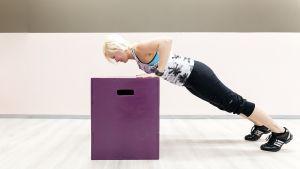 Personal trainer Anu Junnila tekee etunojapunnerrusta laatikkoa vasten.