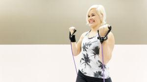Personal trainer Anu Junnila tekee hauiskääntöä kuminauhalla.