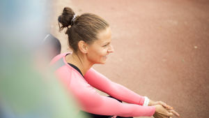Elina Hovinen istuu urheilukentällä ja hymyilee.