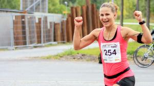 Elina Hovinen juoksee numerolappu rinnassaan ja tuulettaa.