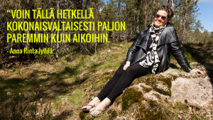 """Anna Rinta-Jyllilä istuu heinikolla metsässä. Kuvassa teksti: """"Voin tällä hetkellä kokonaisvaltaisesti paljon paremmin kuin aikoihin."""