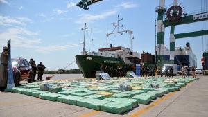 Åtta ton beslagtagen marijuana i gröna paket i hamnen bredvid en båt.