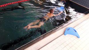 En pojke i en simbassäng