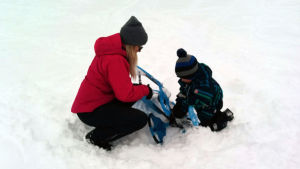 En kvinna med röd jacka hjälper en fyraårig pojke att fixa rattkälken.