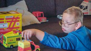 poika leikkii leluautoilla sohvalla