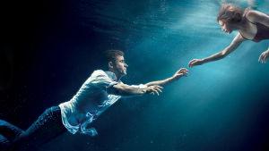 Mies ja nainen kurkottavat toisiaan kohti veden alla.
