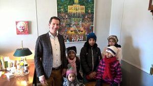 Flyktingbarn poserar tillsammans med Lovisa stadsdirektör.