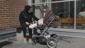 Aysha Waleed Shukait sitter på en bänk utomhus med sin baby i barnvagn.