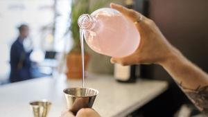 Bar manager Andreas Cederström kaataa vaaleanpunaista raparperisiirappia desimittaan.