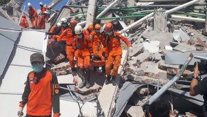 Indonesiska räddningsarbetare bär bort kroppar från en husruin i Palu på söndagen.