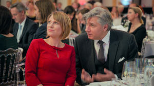 Mies ja nainen istuvat juhlasalissa ruokapöydässä ja katsovat vasempaan.