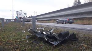 Metallskrot och plastdelar vid vägkanten efter en trafikolycka.