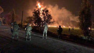 Soldater i förgrunden, en brand i bakgrunden efter att en oljeledning börjar brinna i delstaten Hidalgo i Mexiko.