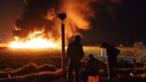 En brand härjar i bakgrunden efter att en oljeledning börjat brinna i Mexiko. I förgrunden tre människor.