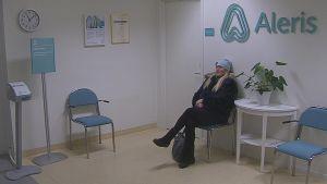Liza Nilsson sitter på en stol i ett väntrum.