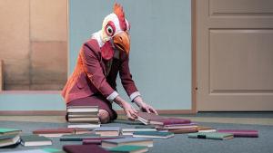 Kanapäinen nainen on polvillaan lattialla, siivoaa sikin sokin leviteltyjä kirjoja. Roolissa Aleksinja Lommi.