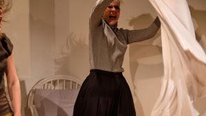 Kati Outinen heiluttaa raivoissaan pussilakanaa. Kuvan reunassa näkyvät myös tanssija Annatuuli Saineen liehuvat hiukset.