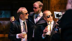 Kolme näyttelijää tummissa puvuissa ja aurinkolaseissa. He ovat lobbareita, jotka juovat kuohuviiniä pahvimukeista. Rooleissa Timo Tuominen, Jani Karvinen ja Markku Maalismaa.