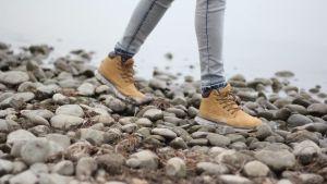 En person går på en stenstrand