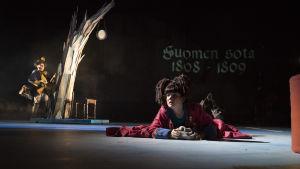 Näytelmän kokija, koiratyttö Alix (Aksa Korttila) Suomen sodassa. Alix makaa maassa, taustalla sotilas Henriikki Remuliini (Petri Liski)