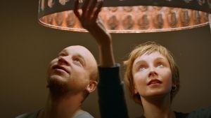 Syskonen Ville och Veera tittar upp mot en lampa med varmt sken.