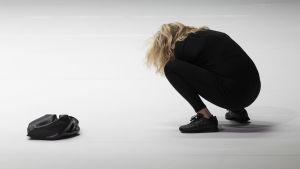 Katariina Kaitueen näyttelemä nainen on kyykistynyt maahan, selin kameraan. Tila on valkoinen, naisella mustat paita ja housut.